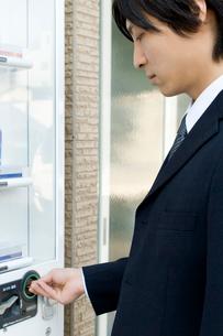 自動販売機で飲み物を買う男性の写真素材 [FYI02963695]