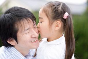 父親にキスをする女の子の写真素材 [FYI02963871]