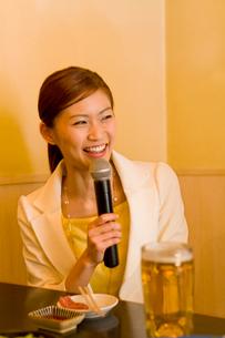 居酒屋でカラオケをする女性の写真素材 [FYI02964298]