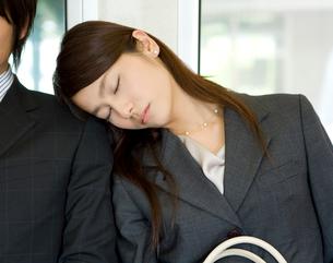 電車の座席に座り居眠りをするOLの写真素材 [FYI02964396]