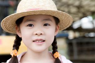 牛舎の前に立つ女の子の写真素材 [FYI02964510]