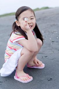 浜辺で貝殻を持っておどける女の子の写真素材 [FYI02964597]