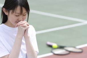 テニスラケットと祈る女子高生の写真素材 [FYI02964606]