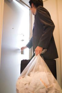 ゴミ袋を持って玄関を出るビジネスマンの写真素材 [FYI02964690]