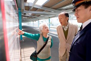 駅の時刻表を見るシニア夫婦の写真素材 [FYI02964745]