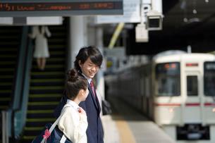 駅のホームで電車を待つ高校生の写真素材 [FYI02964768]