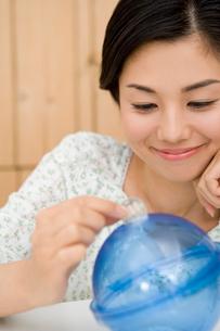 地球の貯金箱にお金を入れる女性の写真素材 [FYI02964800]