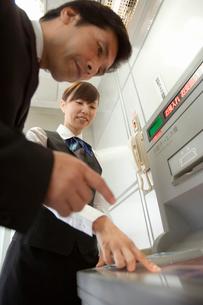ATMの案内をするビジネスウーマンの写真素材 [FYI02964869]