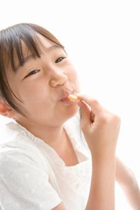 お菓子を食べる女の子の写真素材 [FYI02964912]
