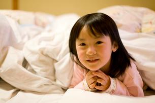 布団に入る笑顔の女の子の写真素材 [FYI02964966]