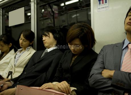 電車内で居眠りをするサラリーマンとOLの写真素材 [FYI02965062]