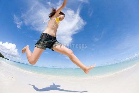 ビーチでジャンプする女性の写真素材 [FYI02965121]