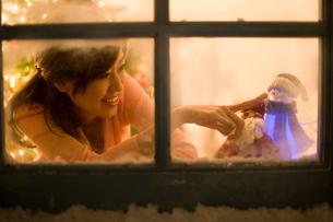 窓辺で人形に触れている女性の写真素材 [FYI02965160]