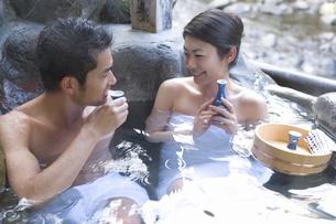 温泉に入りお酒を飲むカップルの写真素材 [FYI02965192]