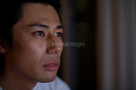 暗い部屋で涙を流す男性の写真素材 [FYI02965247]