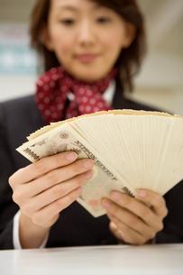 お金を数えるビジネスウーマンの写真素材 [FYI02965270]