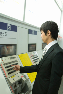 駅で切符を購入するサラリーマンの写真素材 [FYI02965309]