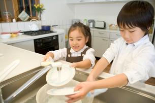 皿洗いをする兄妹の写真素材 [FYI02965314]