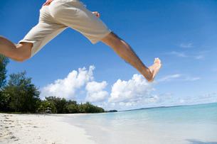ビーチでジャンプする男性の写真素材 [FYI02965342]