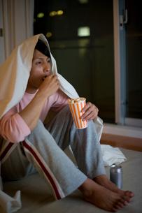 暗い部屋でポップコーンを食べる男性の写真素材 [FYI02965370]