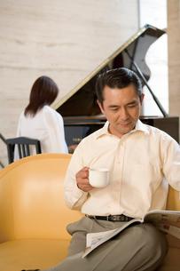 本を見る夫とピアノを弾く妻の写真素材 [FYI02965387]