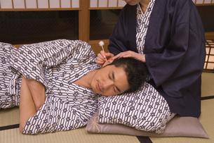 女性の膝枕で耳かきをしてもらう男性の写真素材 [FYI02965418]