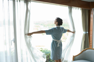 カーテンを開けるメイドの写真素材 [FYI02965423]