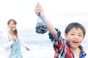 潮干狩りで獲った貝を見せる男の子の写真素材 [FYI02965427]