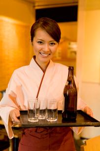 ビールビンとグラスを持つ店員の写真素材 [FYI02965445]