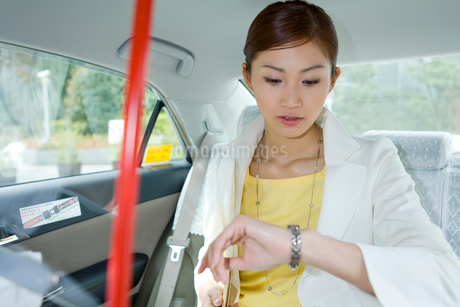 タクシーの中で時計を気にするOLの写真素材 [FYI02965454]