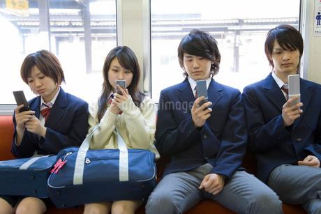 電車の座席に座り携帯電話を見る高校生たちの写真素材 [FYI02965477]