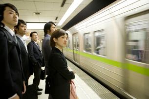 駅のホームに到着した電車を待つ人々の写真素材 [FYI02965500]