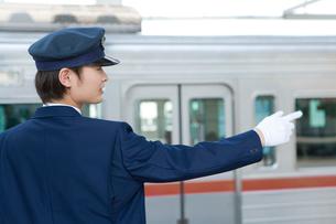 駅のホームで出発のアナウンスをする駅員の写真素材 [FYI02965583]