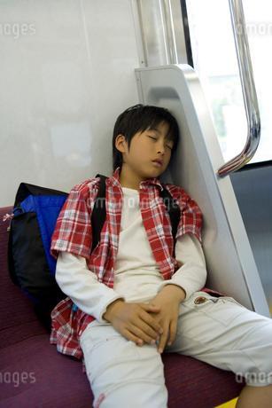 電車内の座席で寝ている男の子の写真素材 [FYI02965618]