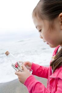 メッセージ入りのビンを手に持った女の子の写真素材 [FYI02965625]