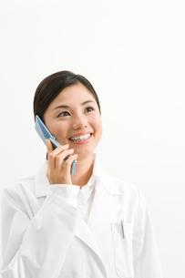 携帯電話で話す白衣の女性の写真素材 [FYI02965648]