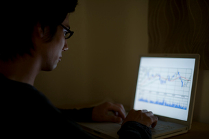暗い部屋でパソコンを見る男性の写真素材 [FYI02965652]