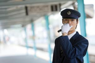 駅のホームでアナウンスをする駅員の写真素材 [FYI02965697]