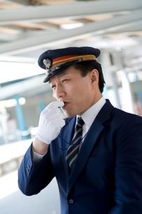 駅のホームで笛を吹く駅員の写真素材 [FYI02965859]
