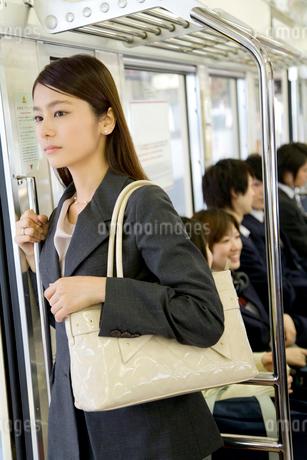 電車内の手すりにつかまる女性の写真素材 [FYI02965972]