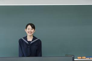 黒板の前に立っている女子高生の写真素材 [FYI02965989]