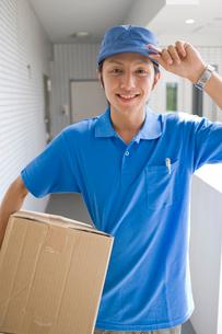 段ボール箱を持つ宅配便屋の男性の写真素材 [FYI02965990]