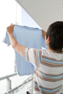 洗濯物を伸ばす男性の写真素材 [FYI02966025]