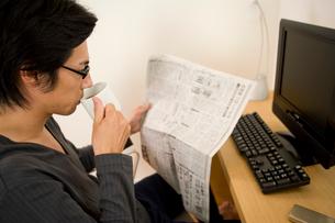 新聞を読みながらコーヒーを飲む男性の写真素材 [FYI02966039]