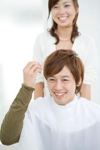 ケープをした笑顔の男性と美容師の写真素材 [FYI02966080]