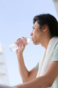 首にタオルをかけて水を飲む男性の写真素材 [FYI02966089]
