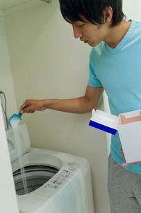 洗濯機に洗剤を入れる男性の写真素材 [FYI02966099]