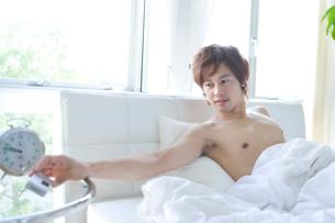 寝起きに携帯電話を見る男性の写真素材 [FYI02966108]