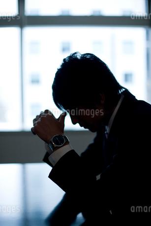 テーブルに座り悩んでいる男性の写真素材 [FYI02966122]