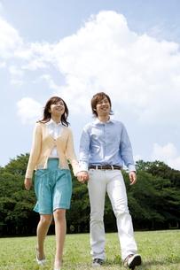 芝生を手を繋いで歩く笑顔のカップルの写真素材 [FYI02966125]